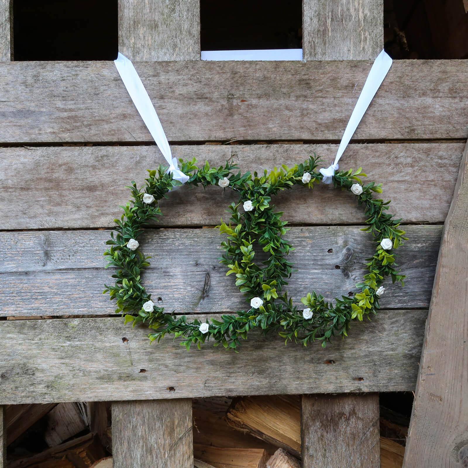 Gebastelte Hochzeitsringe auf einem Holzbrett